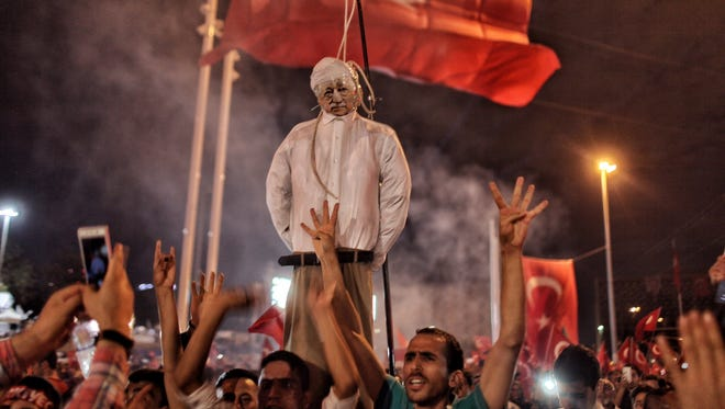 Supporters of Turkish President Recep Tayyip Erdogan hold an effigy of U.S.-based cleric Fethullah Gulen during a pro-government demonstration in Istanbul's central Taksim Square on July 18, 2016.