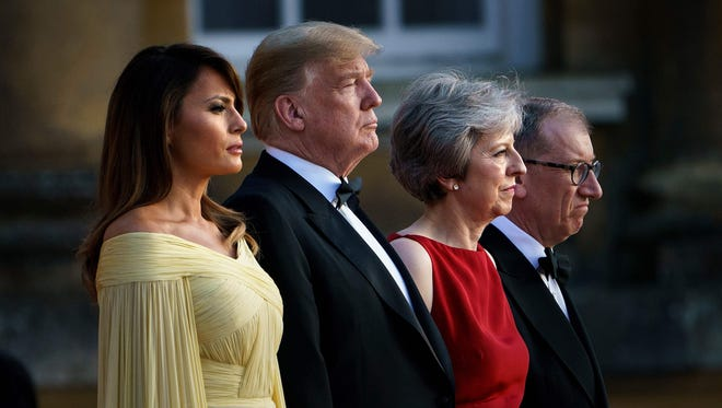 President Donald Trump, Britain's Prime Minister Theresa May, First Lady Melania Trump and Philip May stand on the steps in the Great Court to watch the bands of the Scots, Irish and Welsh Guards perform a ceremonial welcome as they arrive for a black-tie dinner with business leaders at Blenheim Palace, west of London, on July 12, 2018, on the first day of President Trump's visit to the UK.