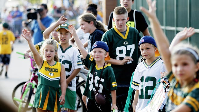 Children eagerly wait for Packers players to pick their bike during the traditional player bike ride from Lambeau Field to Ray Nitschke Field during training camp.