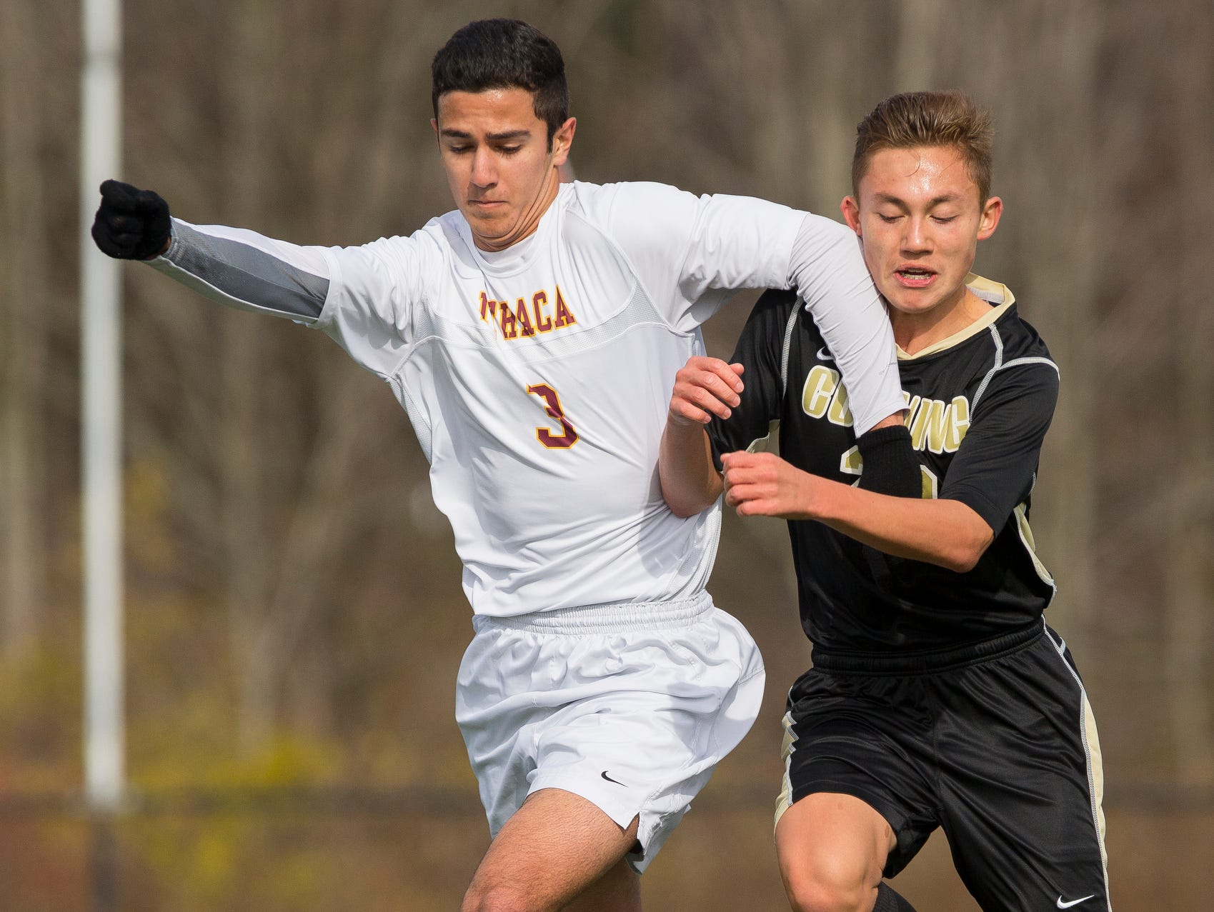 Ithaca's Clayton Curtis, left, holds off Corning's Andrew Araneo Saturday during Ithaca's 2-0 win in the Section IV Class AA game in Oneonta.