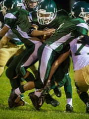 Winooski's Brandon Bigelow, center, squeezes through
