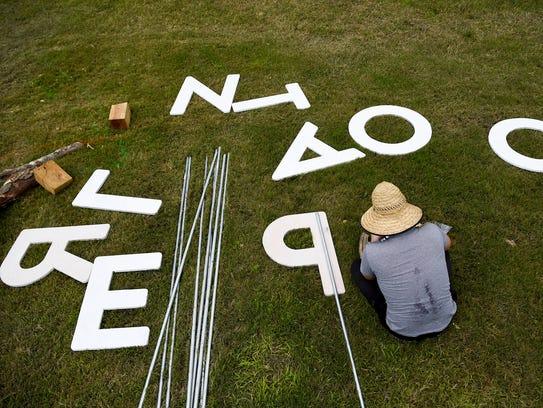 Ben Fieker builds the planet Roo sign in preparation