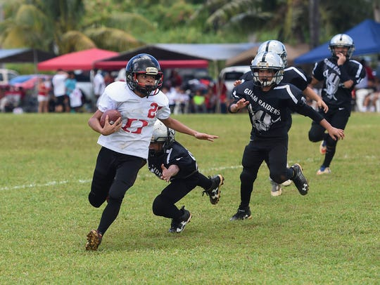 Outlaws player Zavier Camacho eludes a Guam Raiders