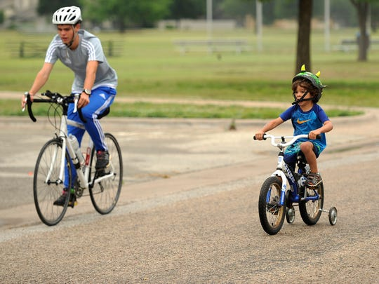 Tucker Batten, 4, rides his bike alongside his older brother, Jaxon, 15, during the YMCA's Kid's Triathlon on June 3, 2017, at Redbud Park. A recent study stressed the importance of forming healthy habits early.