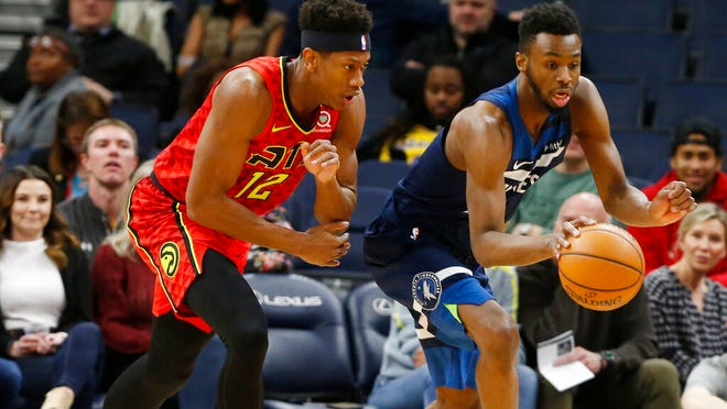 Minnesota Timberwolves' Andrew Wiggins, right, and Atlanta Hawks' De'Andre Hunter chase the ball in the first half of an NBA basketball game Wednesday, Feb. 5, 2020, in Minneapolis.