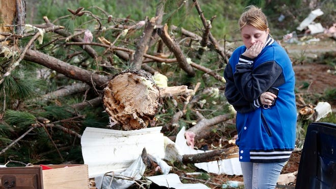 Elizabeth Bordelon walks through the remains of her grandmother's trailer in the Oak Crest Trailer Park in Columbia, Miss., Wednesday, Dec. 24.  Bordelon said her grandmother died during the storm that killed four people in Mississippi.