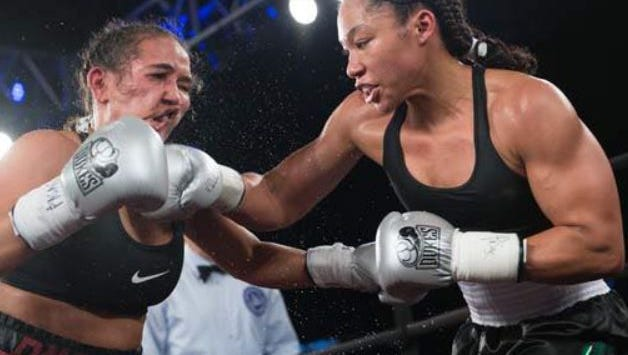 Alycia Baumgardner connects with a right cross on Nydia Feliciano Saturday on her way to a unanimous championship win for the WBC Super Featherweight title.