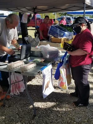 A shopper at the Railcar Farmers Market in Van Alstyne purchases Items from a vendor on Sept. 29. The market runs from 4-7 p.m. Tuesdays through Oct. 27.