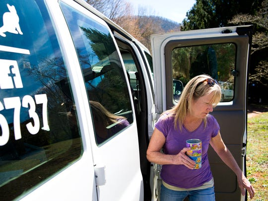 Nancy Schneiter, of Friends2Ferals, retrieves cat food from her van to place in feral cat traps at a mobile home park on Demure Road in Leicester Tuesday April 4, 2017.