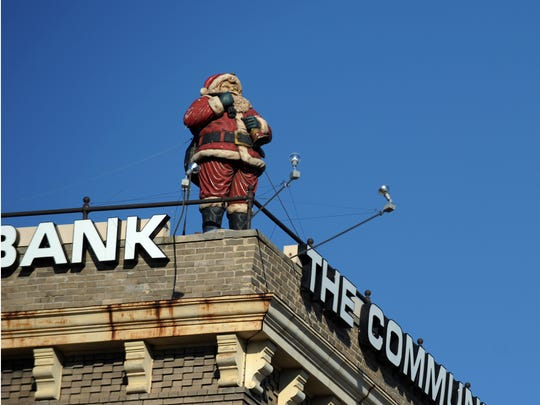 A Santa Claus statue looks over the edge of The Community Bank in downtown Lancaster. This fiberglass statue has been keeping watch over the city since 1999, but various statues have keeping watch from the top of the building for nearly 90 years.