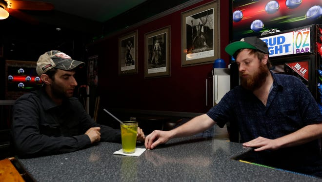 Bartender Ryan Bessette, right, returns changes to Joseph Schoener Monday night at Oz Night Club in downtown Wausau.