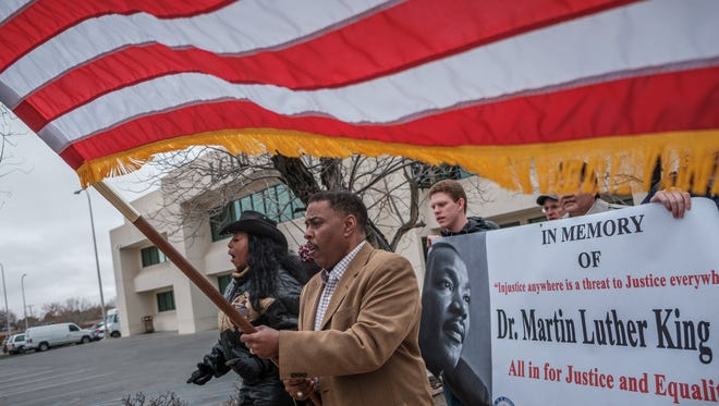 Dr. Bobbie Green, left, leads marchers in singing, while NAACP President Curtis Rosemond, right, carries the U.S. flag on the downtown mall Sunday. A group of locals, including members of the NAACP, gathered to commemorate civil rights leader Martin Luther King Jr.