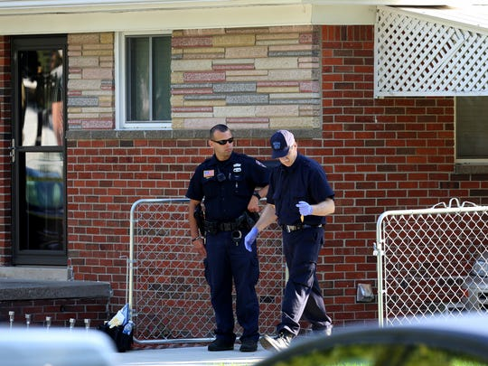 A Dearborn Heights police officer protects the scene