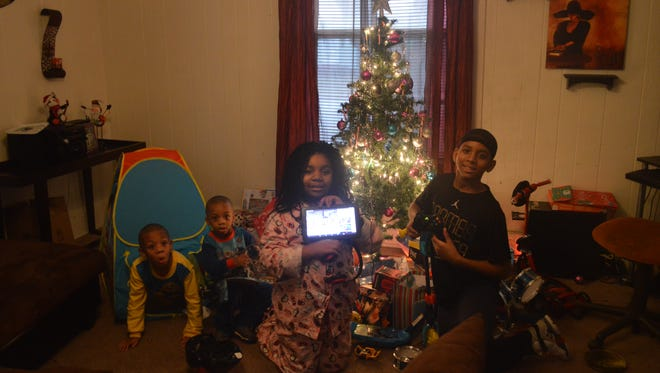Bernice Askew's children, Bryson, Braylen, Erianna and Jason pose in front of the Christmas tree, showing off the gifts they received on Christmas Day.
