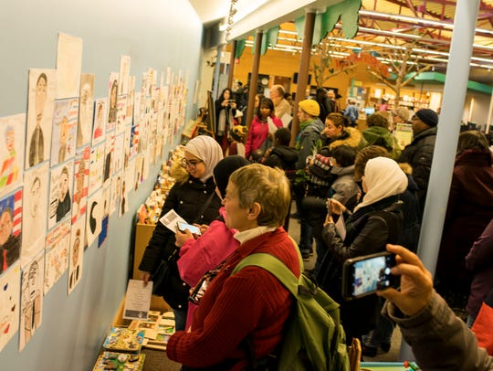 Members of the community admires the art contest entries
