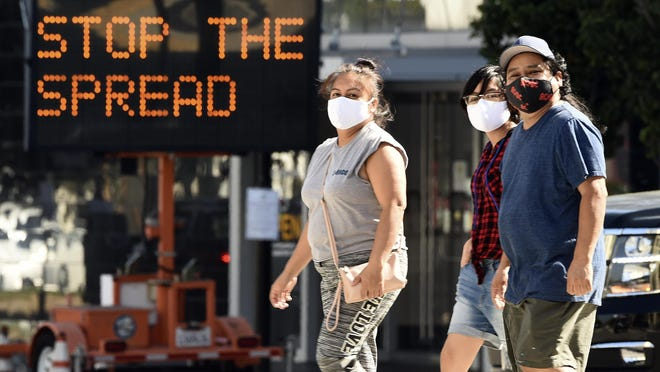Pedestrians wear masks as they walk in front of a sign reminding the public to take steps to stop the spread of coronavirus in Glendale.