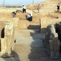 A file picture taken on July 17, 2001 shows Iraqi workers cleaning an archeological site in Nimrud in Iraq. The Islamic State group has begun bulldozing the ancient Assyrian city, the government said, in the jihadists' latest attack on the country's historical heritage.