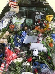 Flowers, art, badges, notes, teddy bears and condolences from friends, family, and people thanking Devin Hodges, Anderson County Sheriff's Office deputy, before the wake on Monday night at the Civic Center of Anderson.