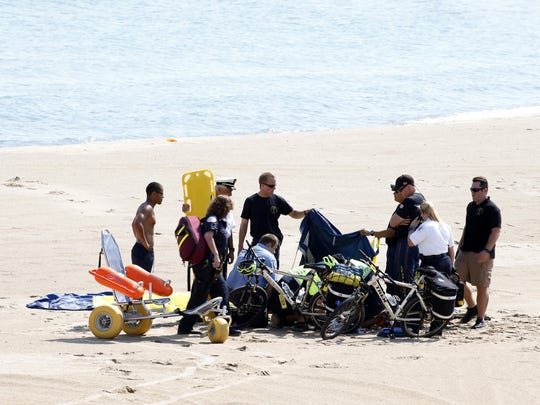 A Navy Leap Frog parachutist receives medical attention on North Avenue Beach on Saturday, Aug. 15, 2015, after a performance at the first day of the annual Chicago Air & Water Show in Chicago.