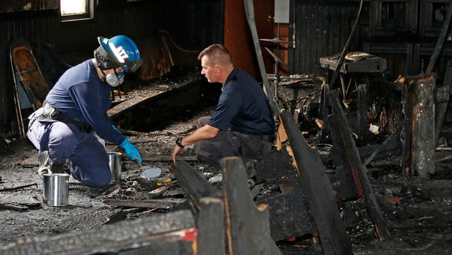 """A state fire marshal, right, and an ATF agent collect evidence as they investigate the fire damaged Hopewell M.B. Baptist Church in Greenville on Nov. 2. """"Vote Trump"""" was spray-painted on an outside wall of the black member church. Fire Chief Ruben Brown said firefighters found flames and smoke pouring from the sanctuary of the church just after 9 p.m. Nov. 1."""