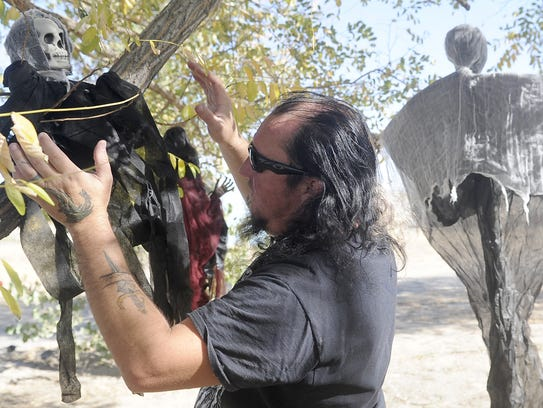 Keith Webb settles a decoration in a tree.
