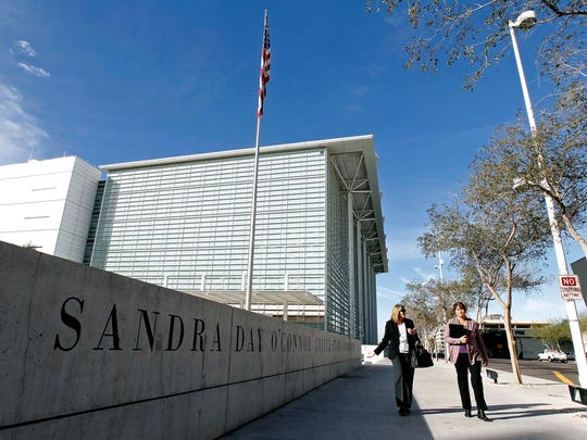 Pedestrians walk past the Sandra Day O'Connor United States District Court where a federal civil rights trial against two polygamous towns on the Arizona-Utah border is set to begin, Tuesday, Jan. 19, 2016, in Phoenix.