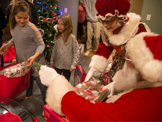Santa's helper Jim Mitchell of Jackson delivers gifts to families who have suffered through catastrophic events this past year. Briana, 9, and Ariana Dugo, 7, receive gifts from Santa.