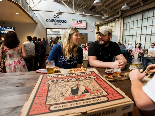 Courtney and Stan  Kindred enjoy pizza and beer as Common Bond Brewers and Bibb Street Pizza Company hold their official openings in Montgomery, Ala., on Saturday April 14, 2018.