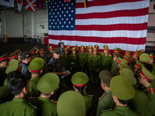 Aviation Ordnanceman 1st Class Don Salice explains damage control capabilities to Vietnamese officials in the hangar bay of the Nimitz-class aircraft carrier USS Carl Vinson during a port visit to Da Nang, Vietnam.