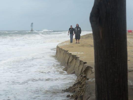 Two gentlemen walk along the Ocean City beach where