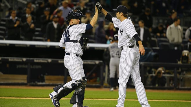 Yankees catcher Brian McCann (left) and closer Andrew Miller celebrate a 4-1 win against the Rays at Yankee Stadium on Monday.