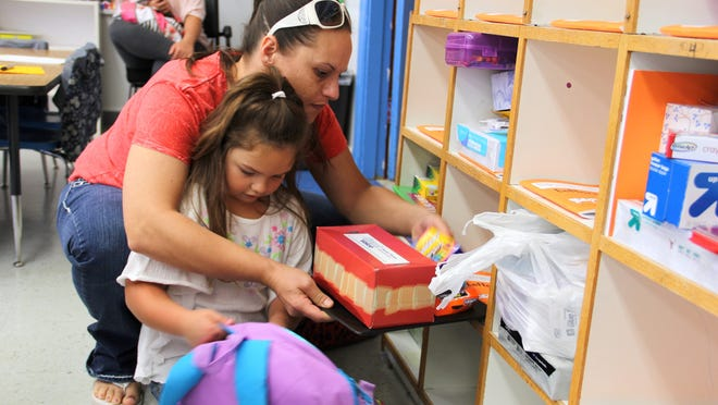 Shawna Manning and her daughter, Faith Bones, 5, put Faith's supplies away during the first day of kindergarten class at Stayton Elementary School on Sept. 4, 2012. Research indicates that full-day kindergarten can enhance student performance in the formative years