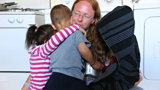 """Amanda Kirkpatrick hugs her three kids for a portrait at the house they moved into from the Missouri Hotel. The Kitchen, Inc. has closed the Missouri Hotel in favor of a new """"housing first"""" approach to helping homeless families."""