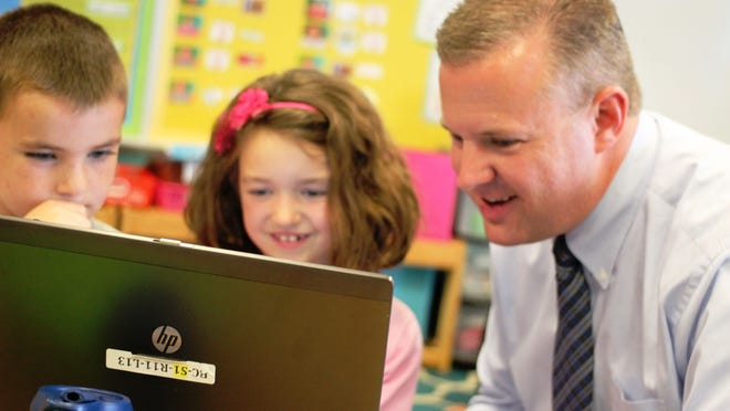 Michael Gabauer and two Burnett Creek Elementary School students use a laptop. Gabauer was appointed principal of Wea Ridge Elementary School May 13, 2015.