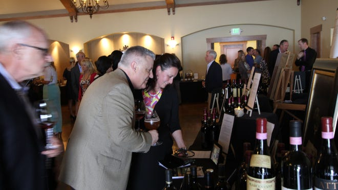 Roth's General Manager Tim Jennings and his wife Jody examine some of the wines up for auction at the Uncorked fundraiser for Family Building Blocks at Zenith Vineyards on Saturday, May 16. 2015.