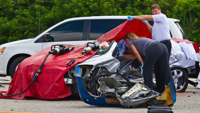 Members of the medical examiners office inspect the body of Joyce Johnson inside a Honda Civic involved in a fatal crash last Tuesday morning at the intersection of US 41 and Evergreen Road in North Fort Myers. The 85-year-old Johnson, a North Fort Myers resident, was the 41st person to die as a result of traffic crash in Lee County this year.