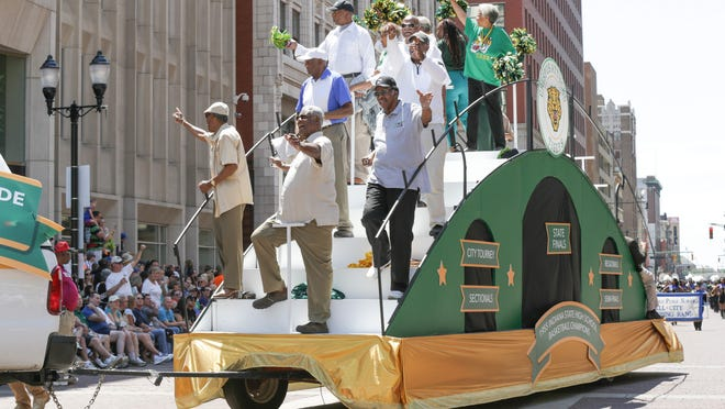 Members of the 1955 Indiana State Basketball Championship team from Crispus Attucks High School, who were chosen as this year's grand marshals of the IPL 500 Festival Parade, make their way on to Monument Circle on Saturday, May 23, 2015.