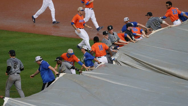 Florida and Vanderbilt players get together to help the grounds crew pull the tarp over the field during a rain delay in the first inning.
