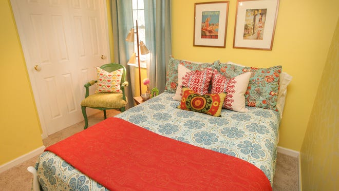 Global prints from Morocco, India, England and Bangkok are mixed to create a colorful, bohemian chic guest room.