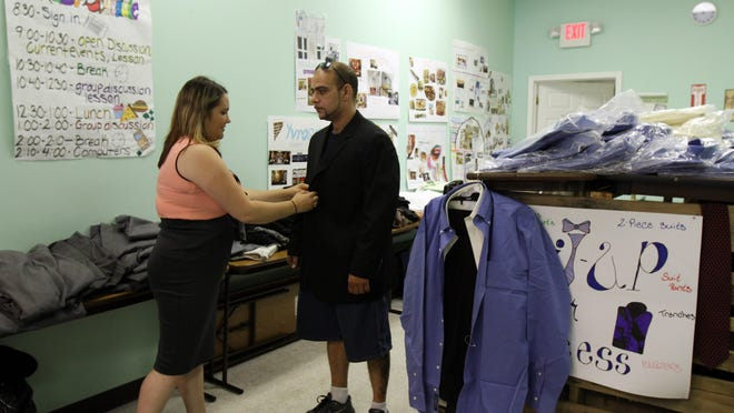 Rachael O'Dea, peer employment specialist, helps Joe Morales of Ocean Gate, a suit recipient, pick the perfect suit as the Tools for Success program hosts a Suit Up for Success event at the Mental Health Association in New Jersey Inc. in Toms River.