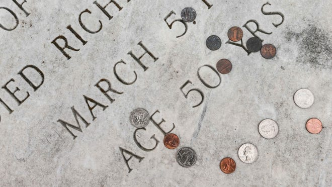 The headstone of the Rev. J.M. Villars, in Holy Cross Cemetery on Indianapolis' Southside, was covered with 87 coins Thursday, June 18, 2015. Some were old and tarnished and hardly recognizable, but some were shiny and dated 2014.