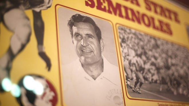 A framed poster of the FSU football team during the 1970's has a photo of then-coach Darrell Mudra and hangs on the wall in his home.