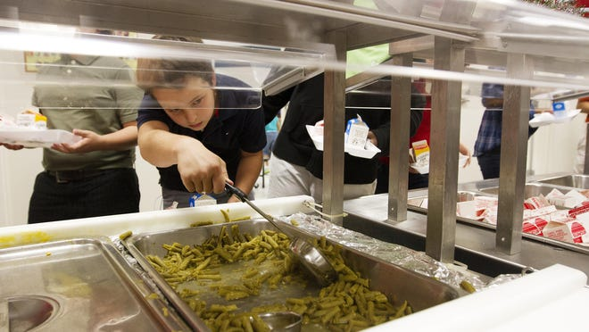 In 2012, an Orangewood Elementary School student scooped green beans onto his plate during lunch at the school.