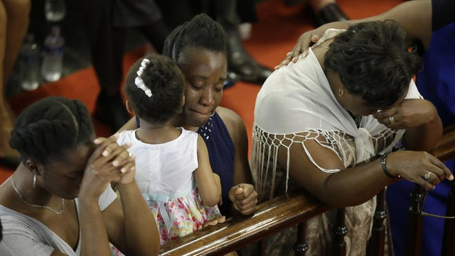 Congregants pray at the Emanuel A.M.E. Church in Charleston, South Carolina on June 21, four days after a mass shooting that claimed nine lives.