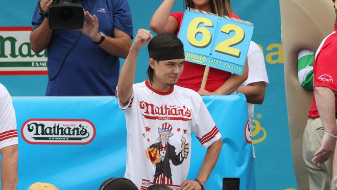 Matt Stonie gestures after winning Nathan's Famous Fourth of July International Hot Dog Eating Contest men's competition Saturday at Coney Island. Stonie ate 62 hot dogs and buns in 10 minutes.