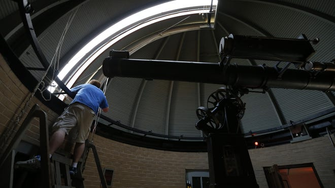 Volunteer and Drake University graduate David Stapleton opens up the observatory dome Friday, July 3, 2015, before visitors get a chance to look through the refractor telescope at the Drake Municipal Observatory in Des Moines.