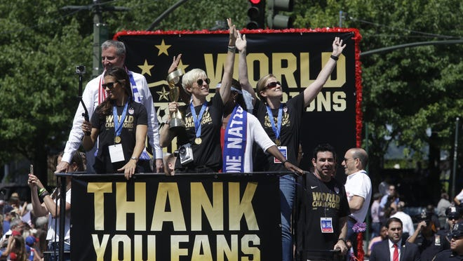 U.S. women's soccer team midfielder Megan Rapinoe, center, holds up the World Cup trophy while midfielder Carli Lloyd, left, New York City Mayor Bill de Blasio, left background, and head coach Jill Ellis, right, wave to the crowd as their float makes it way up Broadway's Canyon of Heroes during the ticker tape parade to celebrate the U.S. women's soccer team World Cup victory, Friday, July 10, 2015, in New York.