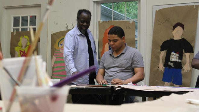 Ouattara Watts, left, and 20-year-old Christian talk about his painting Wednesday at the Rye Arts Center.