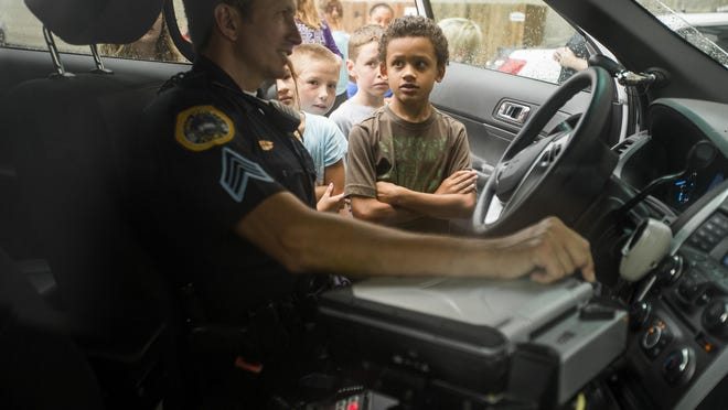 Police Sgt. Paul Parizek shows Mac Fisk of Des Moines, 9, the controls in a police car while giving children from a local child-care center a tour of the Des Moines Police Department on Monday. Chief Dana Wingert wants police efforts to be more community-minded.