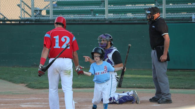 Catholic High graduate Gavin Wehby gives Liberal Bee Jays batboy Kaiser Carlile a high five during a game earlier this year. The nine-year-old Kaiser recently died after being accidentaly struck by a bat.